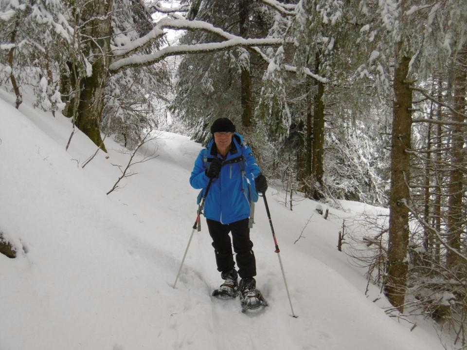 Ein Mann mit Schneeschuhen im verschneiten Wald