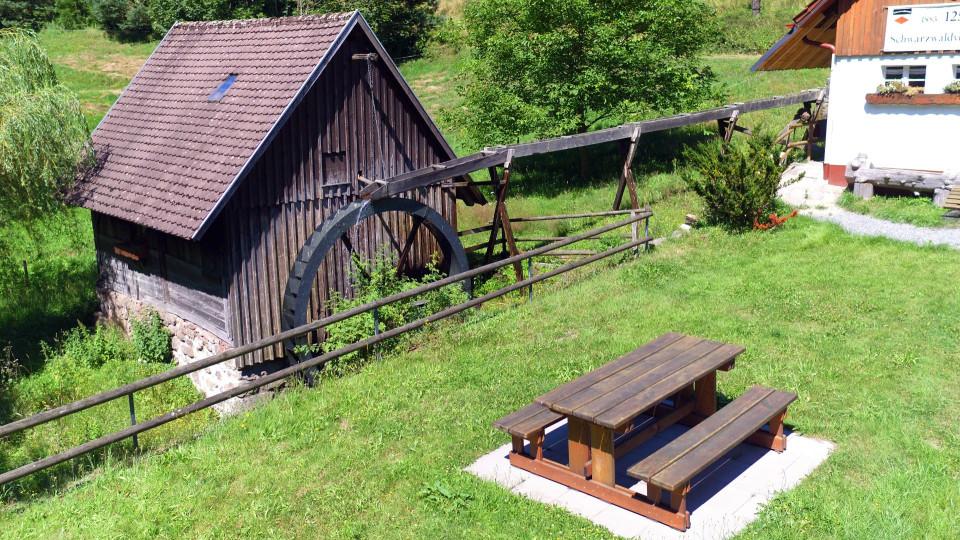 Straßerhofmühle mit Mühlrad und Sitzgruppe vor der Mühle