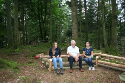 Bürgermeister Scheffold, Frau Gramer und Frau Staiger sitzen auf einer Holzbank im Wald